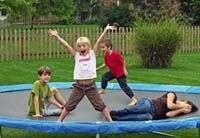 famille sur un trampoline de jardin