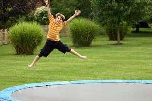 garçon sautant sur trampoline de jardin