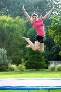 jeune fille sautant sur son trampoline de jardin