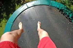 trampoline rond vue du dessus avec les pieds du sauteurs