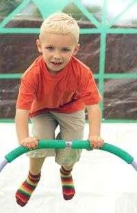 enfant sautant sur mini-trampoline avec barre de maintient